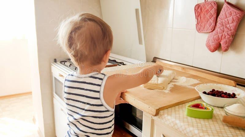 Retrato do close up de 3 da crian?a anos de posi??o do menino na cozinha e na massa do cozimento Cozimento da crian?a e caf? da m imagem de stock