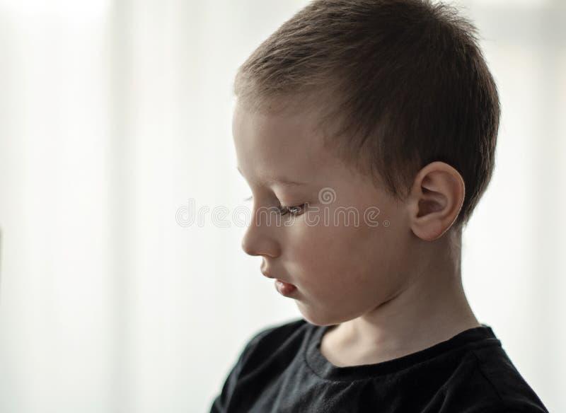 Retrato do close-up de menino novo deprimido do pré-escolar no t-shirt preto que olha para baixo e que pensa Apenas criança infel fotos de stock royalty free