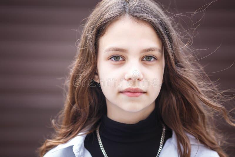 Retrato do close-up de pouca menina à moda bonita da criança com cabelo por muito tempo de fluxo contra uma parede listrada marro fotografia de stock royalty free