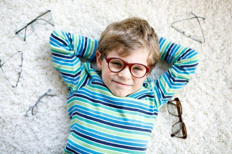 Retrato do close-up de pouco menino louro da criança com os monóculos diferentes no fundo branco Criança de sorriso feliz em ocas fotos de stock