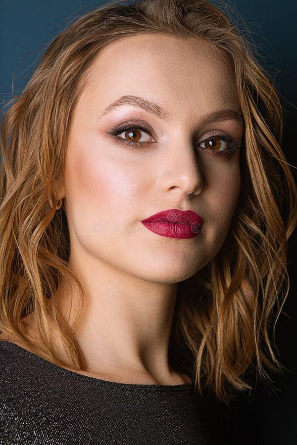 Retrato do close up de surpreender o modelo louro com composição brilhante e cabelo ondulado, levantando no estúdio foto de stock royalty free