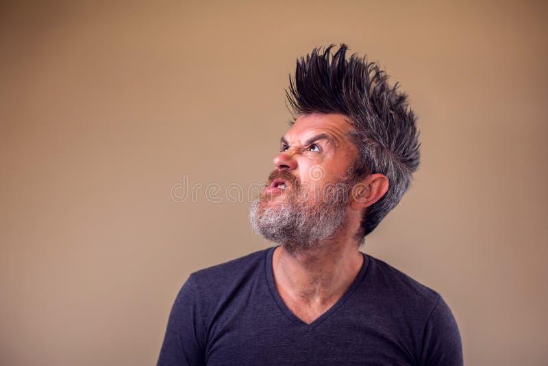 Retrato do close up de um homem adulto irritado com uma barba e do iroquois foto de stock