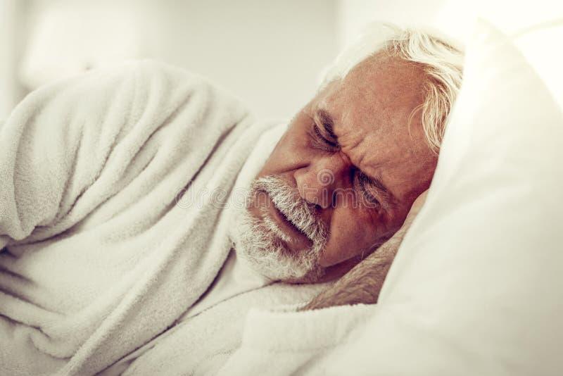 Retrato do close-up de um homem enrugado farpado idoso que experimenta a dor fotos de stock royalty free