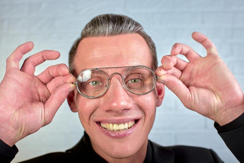Retrato do close up de um homem de negócios novo feliz com os vidros que olham a câmera no fundo branco imagem de stock