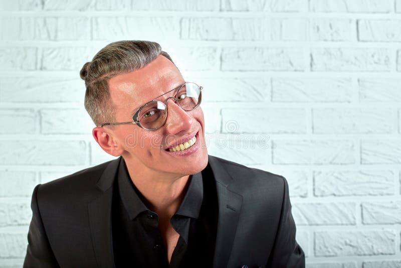 Retrato do close up de um homem de negócios novo feliz com os vidros que olham a câmera no fundo branco imagens de stock