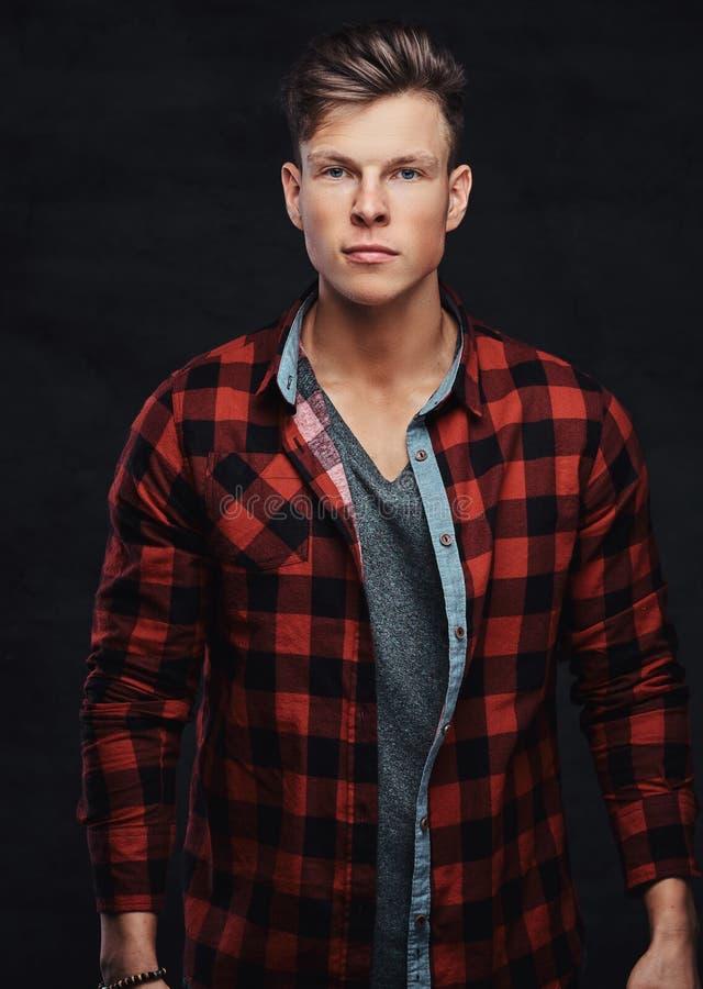 Retrato do close-up de um homem novo considerável em uma camisa do velo, levantando em um estúdio foto de stock