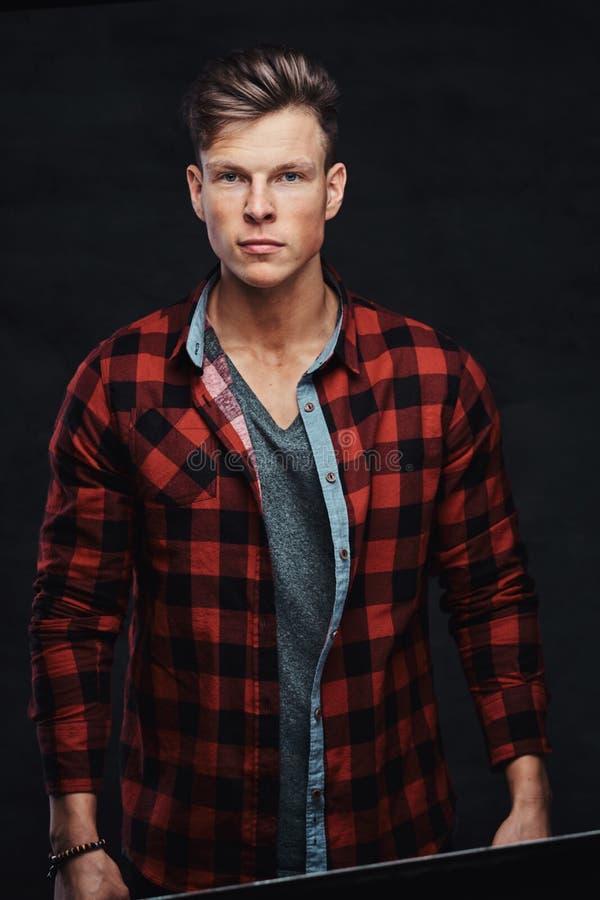 Retrato do close-up de um homem novo considerável em uma camisa do velo, levantando em um estúdio imagem de stock