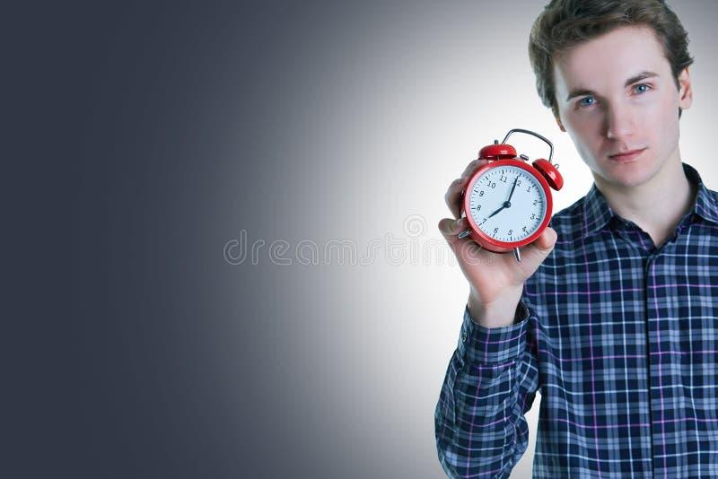 Retrato do close-up de um homem novo incomodado que guarda o despertador sobre o fundo cinzento imagem de stock
