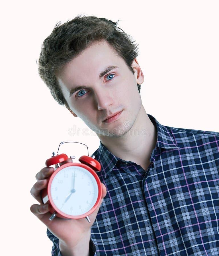 Retrato do close-up de um homem novo incomodado que mantém o despertador isolado sobre o fundo branco imagens de stock royalty free