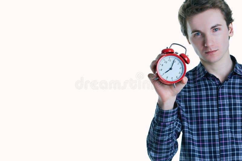 Retrato do close-up de um homem novo incomodado que mantém o despertador isolado sobre o fundo branco fotografia de stock
