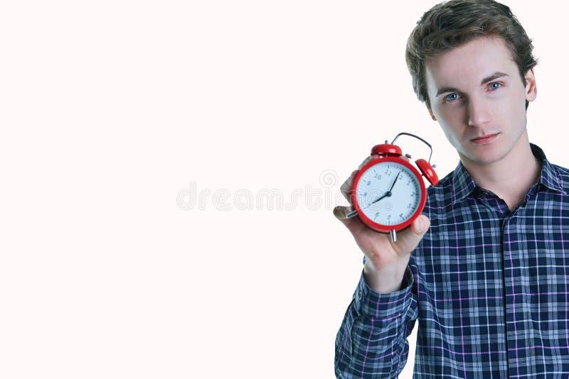 Retrato do close-up de um homem novo incomodado que mantém o despertador isolado sobre o fundo branco fotografia de stock royalty free