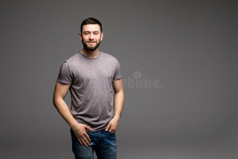 Retrato do close up de um homem novo ocasional que guarda suas mãos em seus bolsos ao olhar na câmera fotos de stock