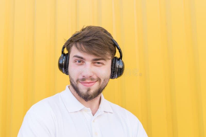 Retrato do close up de um homem novo positivo com os fones de ouvido na cabeça ao escutar a música foto de stock