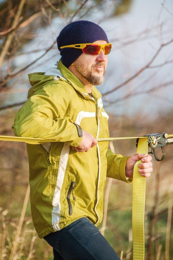Retrato do close-up de um homem que ajusta o equipamento slacklining antes de executar truques slacklining loucos e de andar sobr imagem de stock