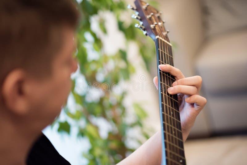 Retrato do close-up de um homem que joga a guitarra acústica imagem de stock royalty free