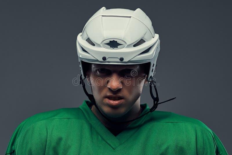 Retrato do close-up de um jogador de hóquei profissional irritado em um sportswear protetor e do capacete em um fundo cinzento foto de stock