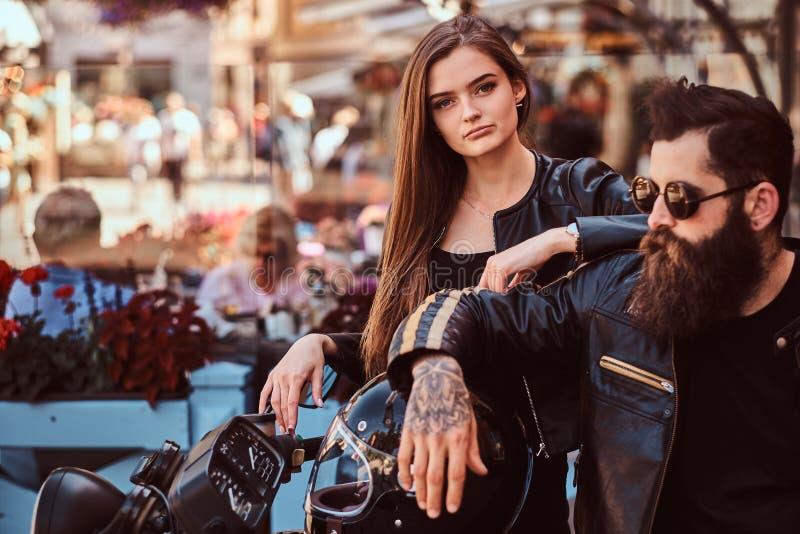 Retrato do close-up de um par do moderno - o homem brutal farpado nos óculos de sol vestiu-se em um casaco de cabedal preto e no  imagens de stock royalty free