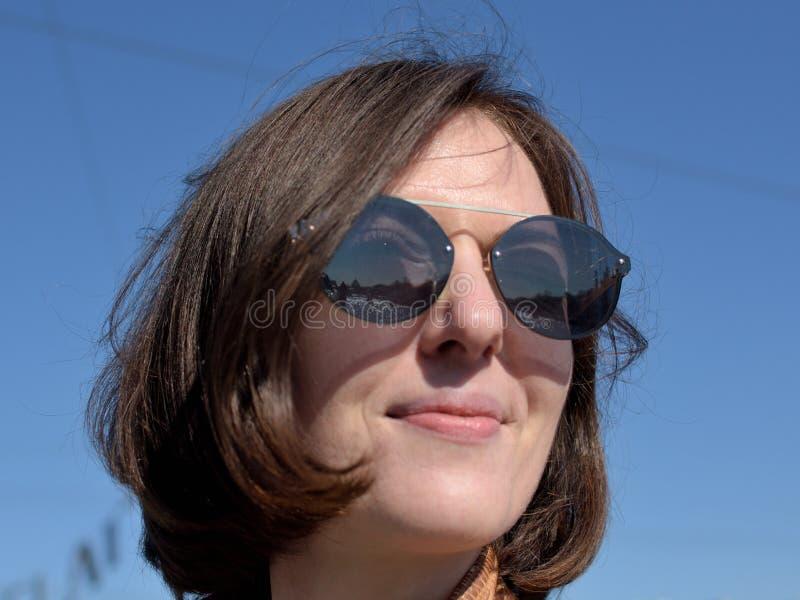 Retrato do close-up de um turista de sorriso da jovem senhora em óculos de sol vestindo de St Petersburg Rússia fotografia de stock