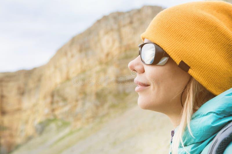 Retrato do close-up de um viajante da menina em um chapéu e em uns óculos de sol de escalada Menina feliz no fundo das rochas imagem de stock royalty free