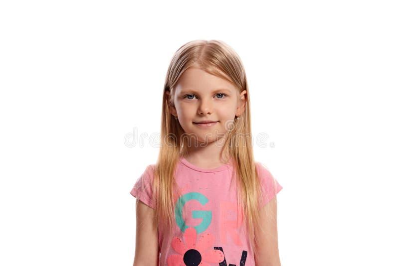 Retrato do close-up de uma criança loura agradável em um levantamento cor-de-rosa do t-shirt isolada no fundo branco imagens de stock