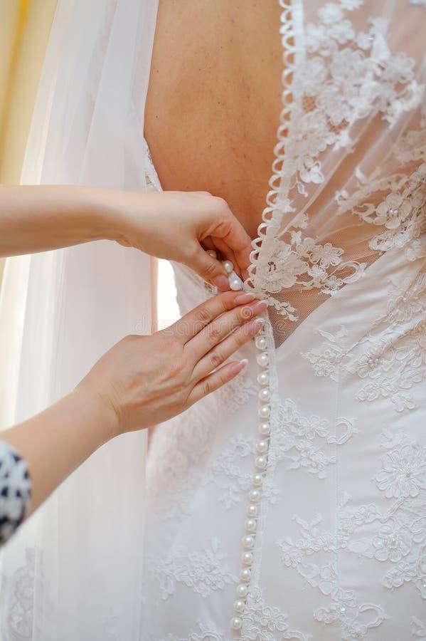 Retrato do close up de uma empregada doméstica de honra que ajuda a noiva com seu vestido foto de stock royalty free