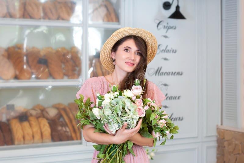 Retrato do close-up de uma jovem mulher atrativa em um chapéu do vestido e de palha do verão, mantendo um ramalhete das flores co fotos de stock