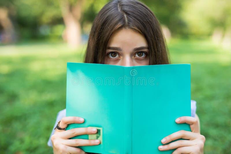 Retrato do close-up de uma jovem mulher bonita com o livro no parque foto de stock royalty free