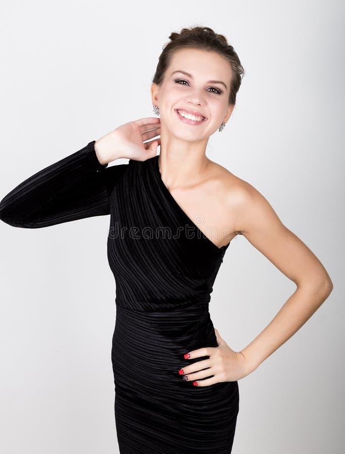 Retrato do close-up de uma mulher bonita 'sexy' em pouco vestido preto da forma, sorrindo foto de stock