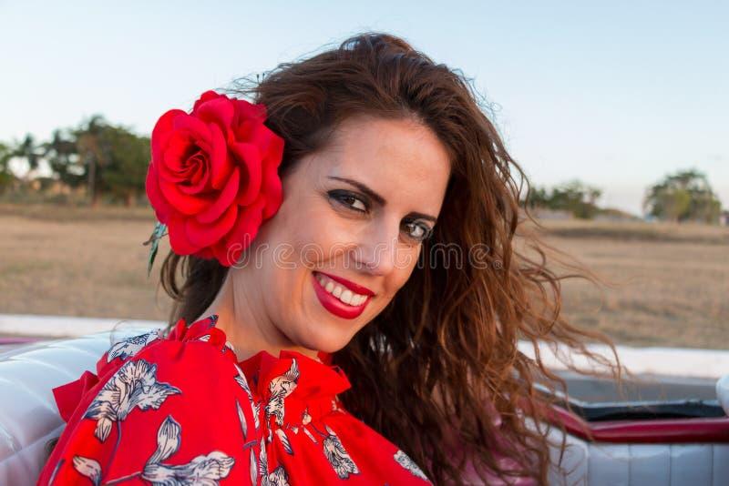 Retrato do close-up de uma mulher moreno nova com seu cabelo acima e um vestido vermelho com uma flor vermelha em seu cabelo imagens de stock royalty free