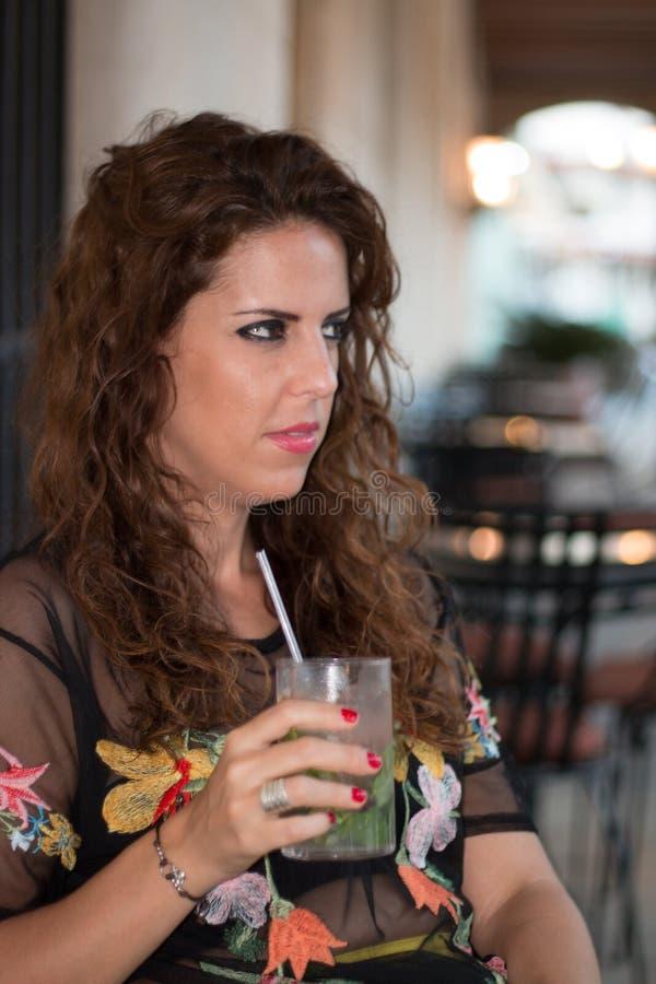 Retrato do close up de uma mulher moreno nova em um terraço que bebe um mojito fotografia de stock