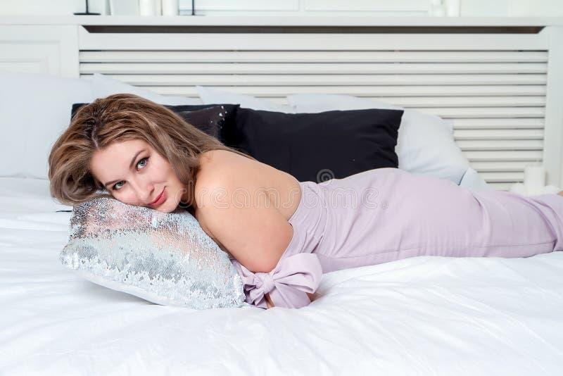 Retrato do close up de uma mulher de sorriso bonita que encontra-se na cama fotografia de stock royalty free