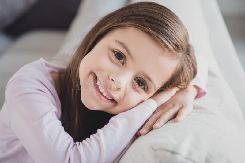Retrato do close-up dela ela menina pre-adolescente animador alegre atrativa adorável encantador agradável que senta-se no divã d fotos de stock royalty free