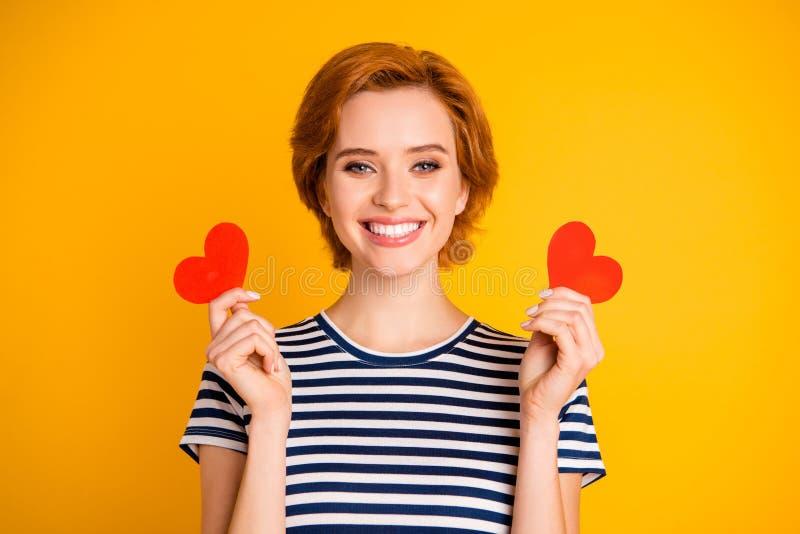 Retrato do close-up dela ela queolha a menina alegre atrativa doce bonita que realiza no coração pequeno pequeno das mãos dois imagens de stock