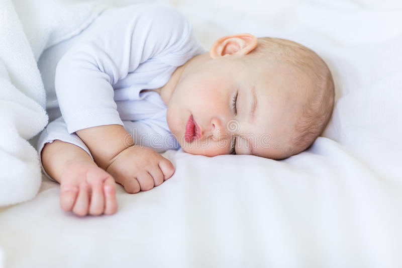 Retrato do close-up do bebê adorável que dorme na cama fotografia de stock