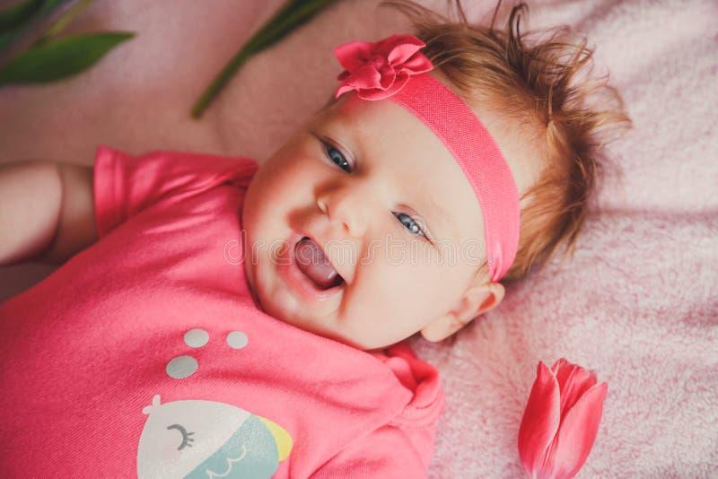 Retrato do close-up do bebê de sorriso feliz bonito que encontra-se para baixo na cama cor-de-rosa com tulipas ao redor fotografia de stock royalty free