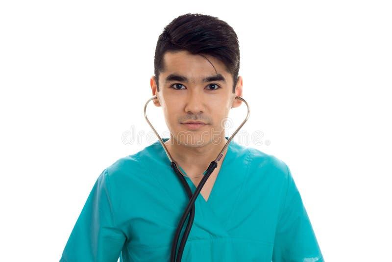 Retrato do close up do doutor moreno considerável novo do homem no uniforme azul com o estetoscópio que olha a câmera isolada fotografia de stock