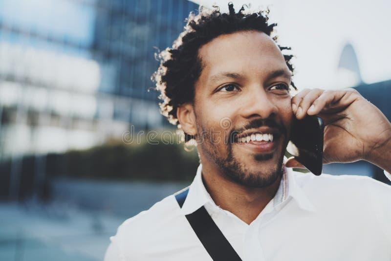 Retrato do close up do homem africano americano feliz que usa o smartphone para chamar seus amigos na cidade ensolarada Conceito  fotos de stock