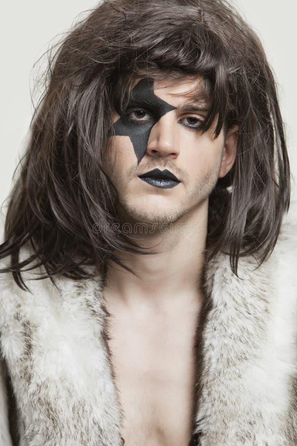 Retrato do close-up do homem novo sério com a cara pintada sobre o fundo cinzento fotos de stock