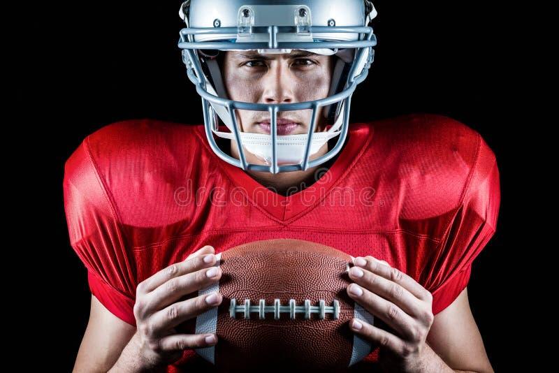 Retrato do close-up do jogador de futebol americano seguro que guarda a bola fotografia de stock