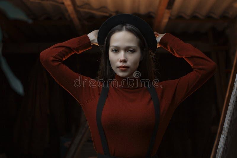 Retrato do close-up do mulheres elegantes novas bonitas Senhora que levanta na obscuridade - fundo cinzento Vestir modelo à moda fotografia de stock
