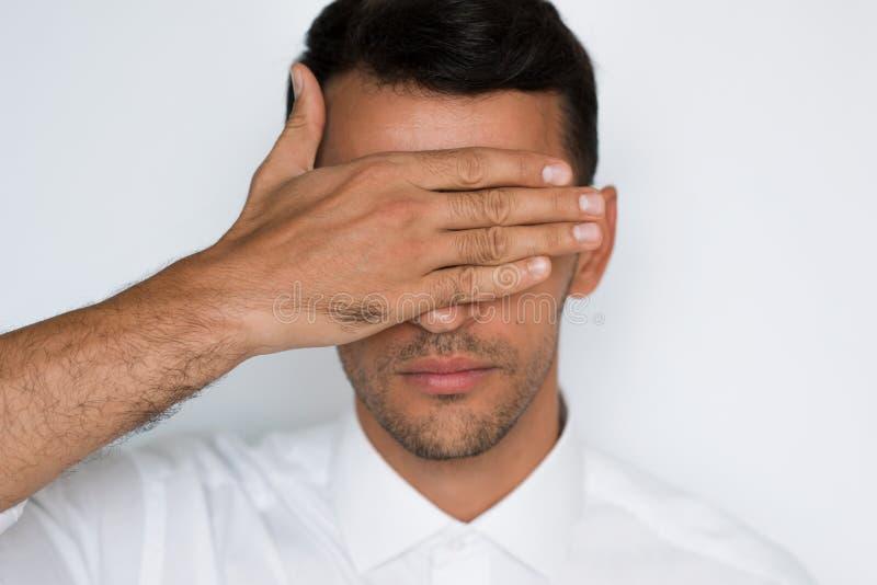 Retrato do close-up dos olhos consideráveis da tampa do homem com a mão isolada no fundo cinzento Proteção de olhos vendados do h fotografia de stock royalty free