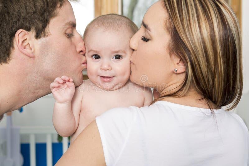 Retrato do close up dos pais novos que beijam o filho recém-nascido bonito imagem de stock royalty free