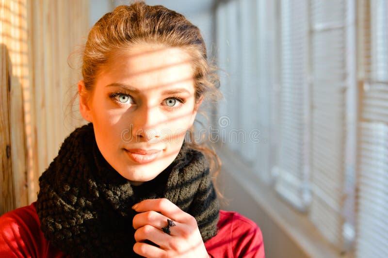 Retrato do close up em olhar a jovem mulher bonita maravilhosa da câmera com olhos azuis no xaile em um fundo da janela do balcão imagem de stock