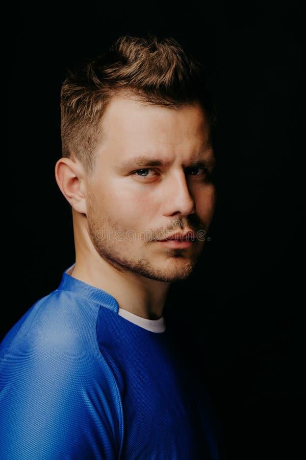 Retrato do close-up do futebol considerável novo do jogador de futebol que levanta no fundo escuro preto foto de stock