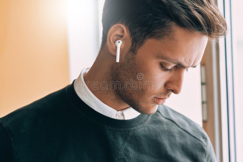 Retrato do close up do homem considerável novo triste que fala com um amigo que usa fones de ouvido sem fio foto de stock