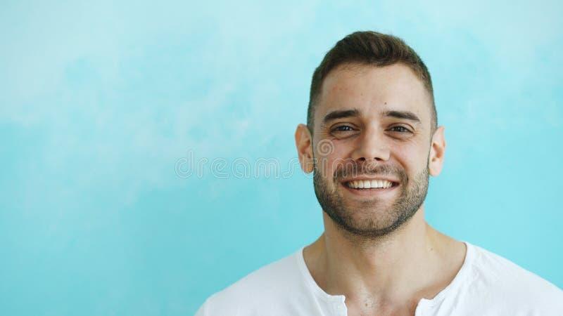 Retrato do close up do homem de sorriso e de riso novo que olha na câmera no fundo azul imagens de stock