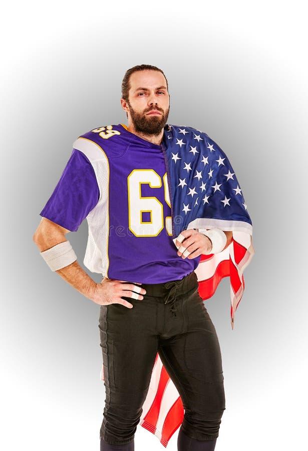 Retrato do close up do jogador de futebol americano Jogador de futebol americano com uma bandeira americana em suas mãos Conceito imagem de stock royalty free