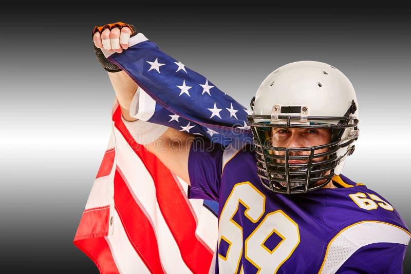 Retrato do close up do jogador de futebol americano Jogador de futebol americano com uma bandeira americana em suas mãos Conceito fotografia de stock