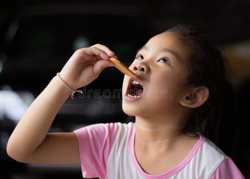 Retrato do close up, menina que come uma cookie, alimento, menina que guarda a cookie fotos de stock royalty free
