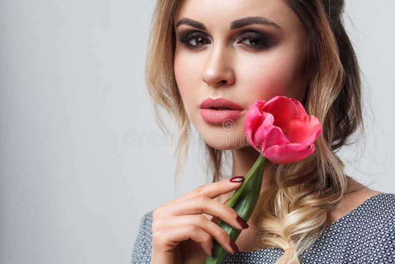 Retrato do close up do modelo de forma atrativo bonito no vestido cinzento com a tulipa da terra arrendada da composição e do pen foto de stock